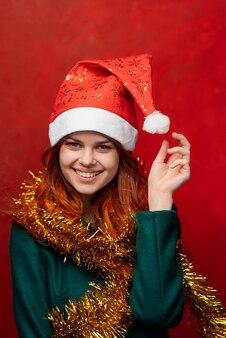 Wesołych świąt kobieta w nowym roku w czapkę i blichtr, jasna ściana