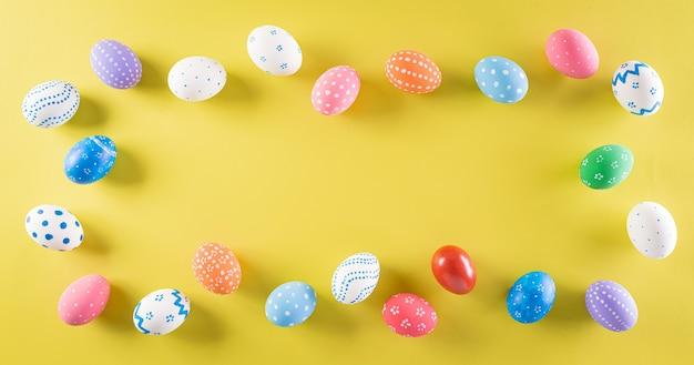 Wesołych świąt kolorowe pisanki na pastelowy żółty