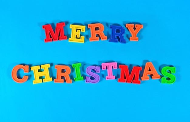 Wesołych świąt kolorowy tekst na niebieskim tle