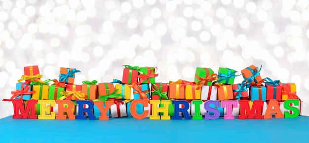 Wesołych świąt kolorowy tekst na tle różnokolorowych prezentów na tle bokeh