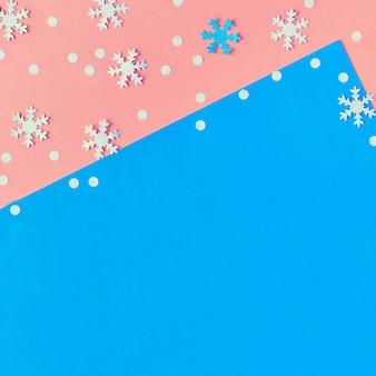 Wesołych świąt! kreatywne papierowe mieszkanie leżało w kolorze różowym, niebieskim i białym ze płatkami śniegu