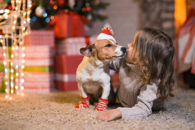 Wesołych świąt. mała dziewczynka dziecko w domu przy kominku z psem jack russell terrier w czerwone białe skarpetki i choinka z prezentami i świecącymi girlandami świętuje boże narodzenie