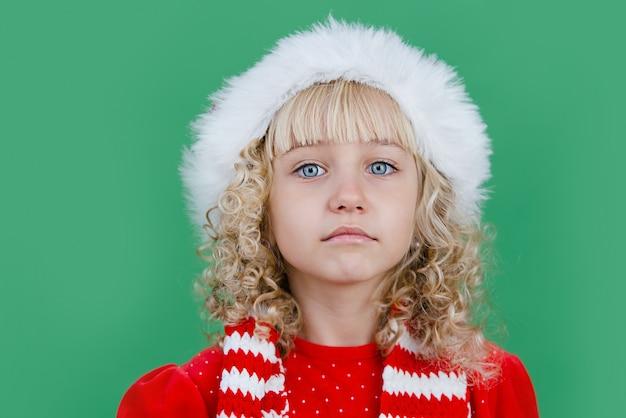Wesołych świąt mała dziewczynka w santa hat na jasny zielony