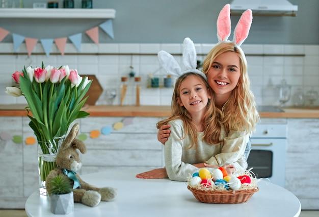 Wesołych świąt! matka i córka bawią się w kuchni. rodzina przygotowuje się do wielkanocy. cute little girl dziecko nosi uszy królika.