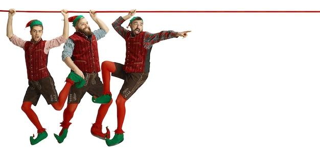 Wesołych świąt mikołaje elfy wspinają się po linie na białym tle studia