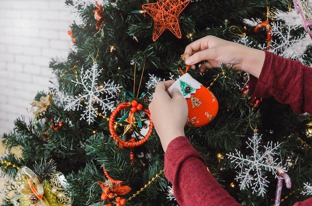 Wesołych świąt. młoda kobieta ręka w czerwonym swetrze dekorowanie na pięknej choinki w domu