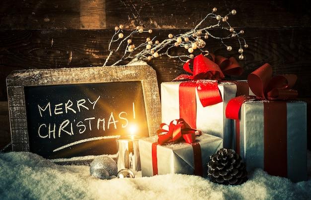 Wesołych świąt na tabliczce z prezentami i świeczką.