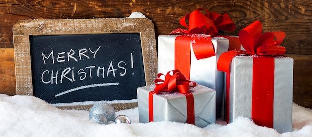 Wesołych świąt na tabliczce z prezentami, widok panoramiczny.