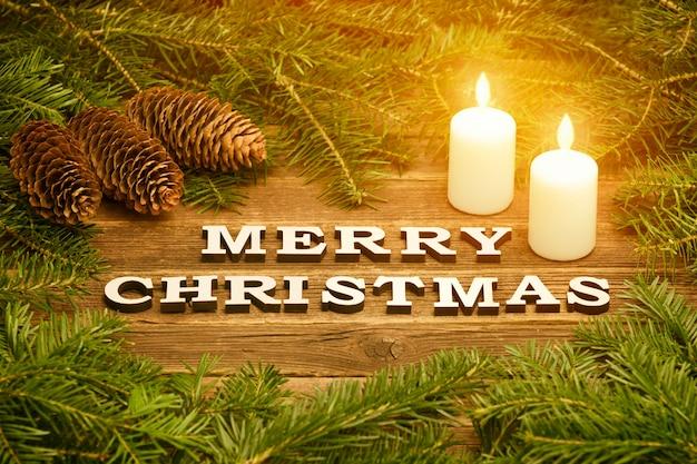 Wesołych świąt napis na drewnianym tle. rama z gałązek jodły, szyszek i zapalonych świec