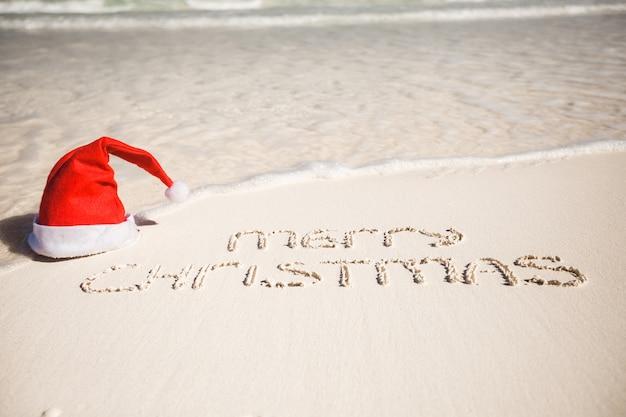 Wesołych świąt napisanych na tropikalnej plaży biały piasek z kapeluszem boże narodzenie