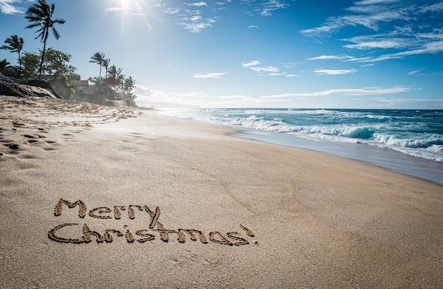 Wesołych świąt napisanych w piasku na sunset beach na hawajach z palmami i oceanem