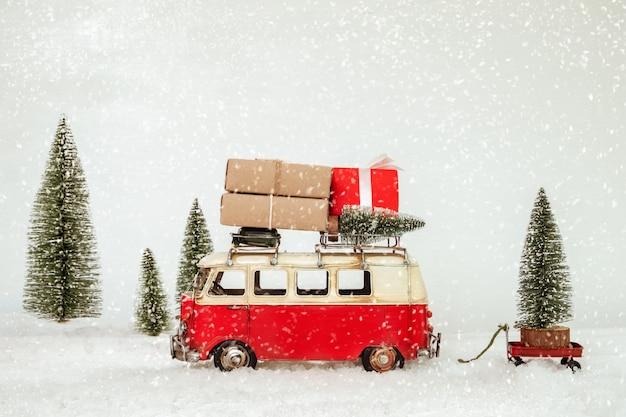 Wesołych świąt pocztówka tło - miniaturowy zabytkowy samochód przewożący prezenty (pudełko) na dachu i choinki w śnieżnym zimowym lesie.