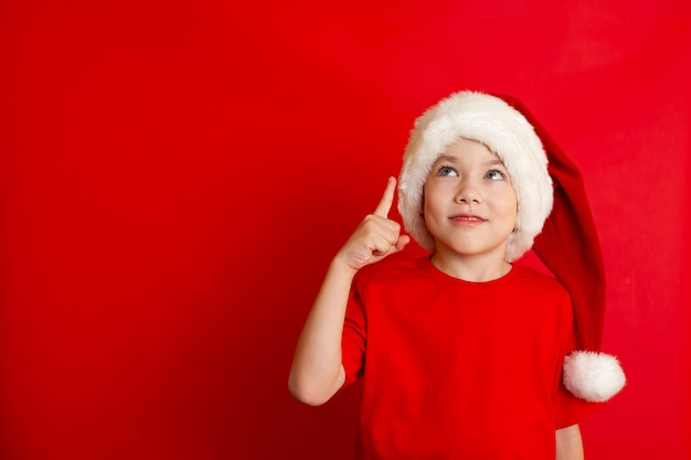 Wesołych świąt. portret ładny wesoły chłopak w świątecznej czapce w czerwonej koszulce na czerwonym tle. miejsce na tekst. zdjęcie wysokiej jakości