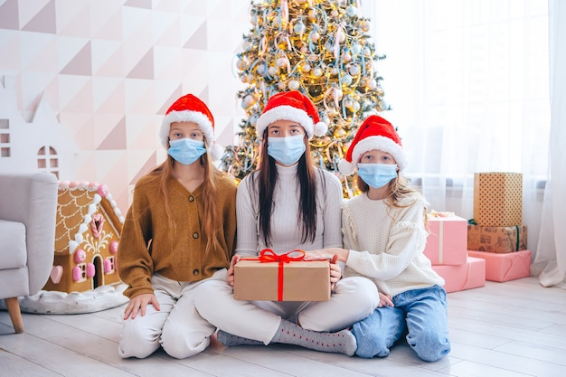 Wesołych świąt. rodzina mamy i dzieci z prezentami na boże narodzenie. rodzice i dzieci noszą maski na twarz
