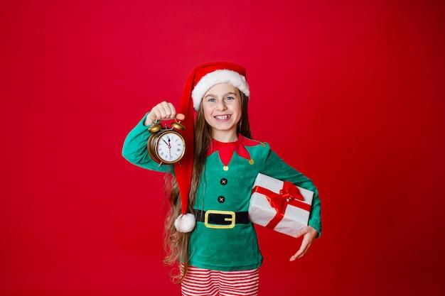 Wesołych świąt, szczęśliwa atrakcyjna dziewczyna z zegarem i prezentami w stroju pomocnika świętego mikołaja