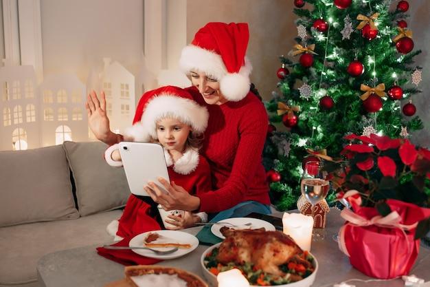 Wesołych świąt szczęśliwa mama i córka jedzą kolację i wideo pozdrowienia dla jego taty