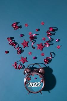 Wesołych świąt szczęśliwego nowego roku płasko leżące z budzikiem, gwiazdami, serpentynami numer 2022 w formacie pionowym
