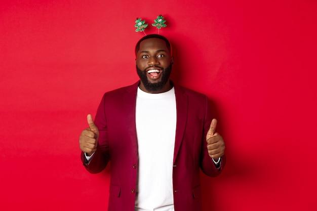 Wesołych świąt. szczęśliwy afroamerykanin świętujący nowy rok, ubrany w zabawną opaskę na imprezę i pokazujący kciuk w górę, jak i chwalący coś, stojąc nad czerwonym backgrond