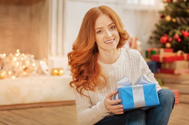 Wesołych świąt. urocza dojrzała pani siedząca na podłodze trzymając pięknie zapakowany prezent.