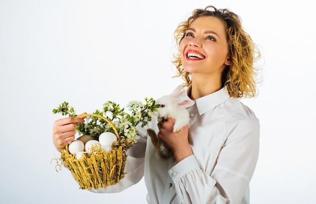 Wesołych świąt, uśmiechnięta kobieta z białym królikiem i koszem z jajkami.