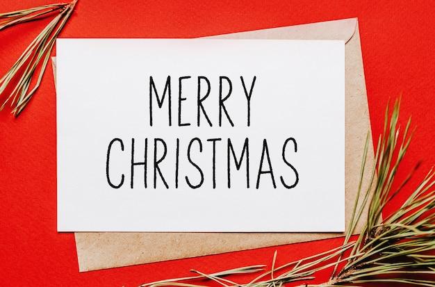 Wesołych świąt uwaga z gałęzi jodły na czerwonym tle na białym tle. koncepcja nowego roku