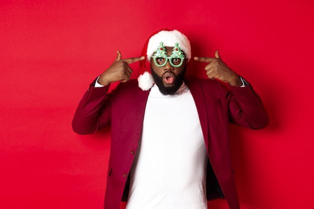 Wesołych świąt. wesoły murzyn w zabawnych imprezowych okularach i czapce mikołaja, uśmiechnięty radośnie, świętujący ferie zimowe, stojący na czerwonym tle