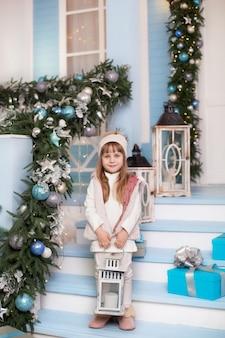 Wesołych świąt, wesołych świąt! . mała dziewczynka stoi z dużą lampką świąteczną na werandzie domu. dziecko ozdabia zimowy taras na powierzchnię. piękne dziecko dziewczynka stoi z latarnią