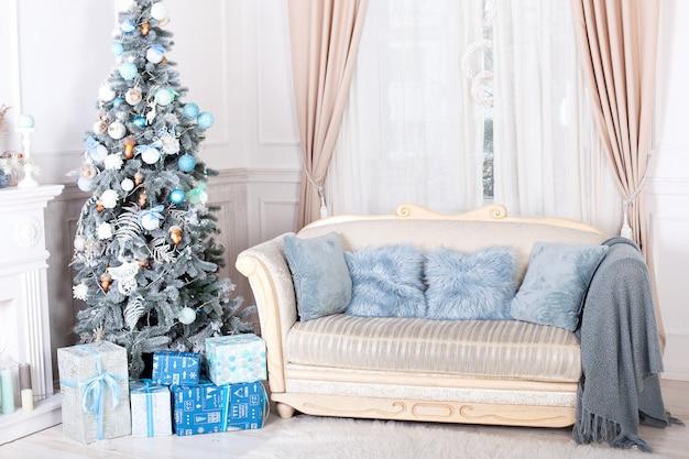 Wesołych świąt, wesołych świąt. stylowe wnętrze salonu z ozdobną choinką, kominkiem i wygodną sofą. choinka z prezentami poniżej. wnętrze noworoczne.