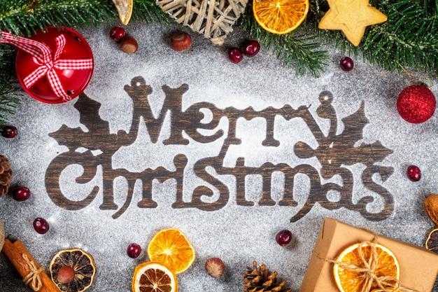 Wesołych świąt westchnienie wykonane z cukru w proszku otoczone ozdobą świąt bożego narodzenia, płasko