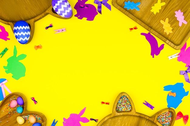 Wesołych świąt wielkanocnych. drewniane talerze w kształcie serca, kwadrat z kolorowymi pisankami z komiksową twarz na żółtym tle