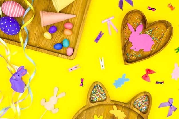 Wesołych świąt wielkanocnych. drewniane talerze w kształcie serca, kwadratowe z kolorowymi pisankami z komiksową twarzą
