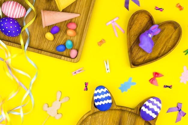 Wesołych świąt wielkanocnych. drewniane talerze w kształcie serca, kwadratu i kota z kolorowymi pisankami, rożkiem waflowym i królikiem z kolorowymi kokardkami i taśmami
