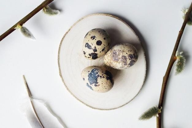 Wesołych świąt wielkanocnych kartkę z życzeniami. jajka przepiórcze na drewnianym talerzu z gałązkami wierzby.