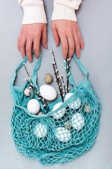 Wesołych świąt wielkanocnych. kobiece ręce trzymają niebieski worek sznurkowy z jajami kurzymi i przepiórczymi oraz gałązkami wierzby na szarym tle