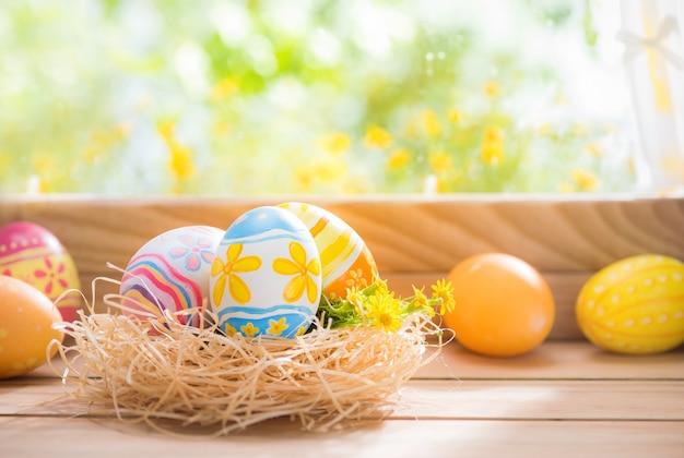 Wesołych świąt wielkanocnych kolorowe jaja w gnieździe i kwiat na drewnie przy oświetleniu okna z miejsca na kopię