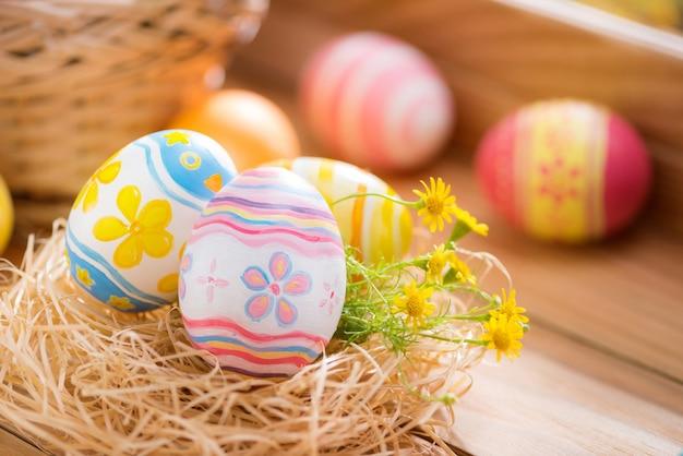 Wesołych świąt wielkanocnych kolorowe jaja w gnieździe i kwiat na drewnie z oświetleniem okna