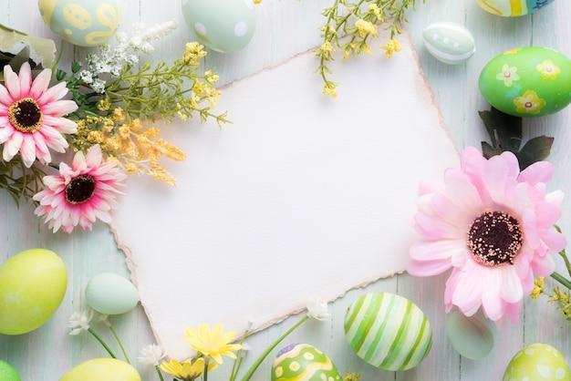 Wesołych świąt wielkanocnych kolorowe jajka i dekoracje kwiatowe na drewnie