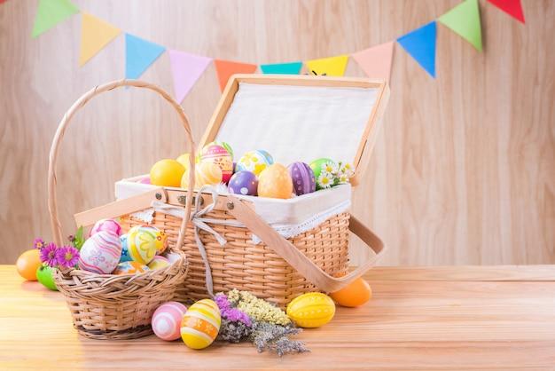 Wesołych świąt wielkanocnych kolorowe jajka i kwiaty w koszu na drewnianej podłodze niewyraźne świętować flagi partii