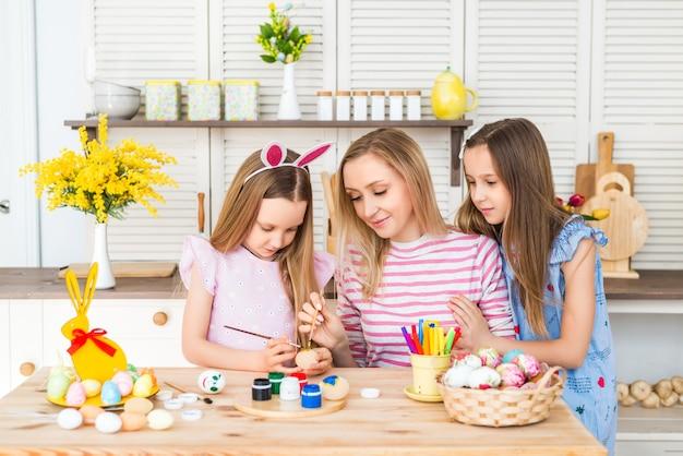 Wesołych świąt wielkanocnych. matka i córki rysują pisanki. szczęśliwa rodzina przygotowuje się do wielkanocy. śliczna mała dziewczynka nosi uszy królika w wielkanocny dzień.
