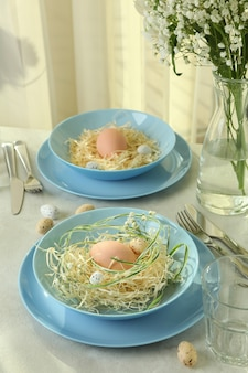Wesołych świąt wielkanocnych nakrycie z jajkami na białym stole z teksturą