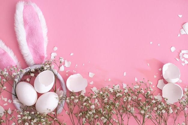 Wesołych świąt wielkanocnych. płaskie układanie wielkanocnych uszu i kwiatów łyszczec na różowym tle. tło wielkanoc. koncepcja wielkanocna