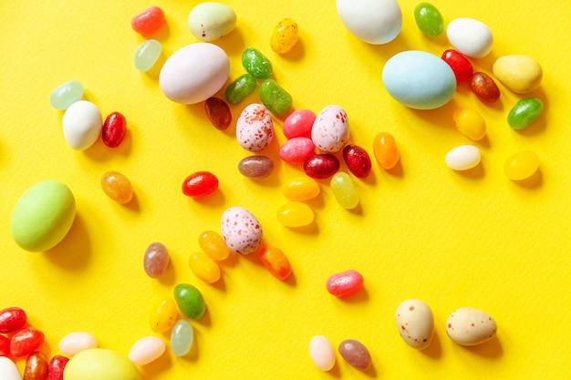 Wesołych świąt wielkanocnych. przygotowanie do wakacji. wielkanocne cukierki czekoladowe jajka i słodycze galaretki na białym tle na modnym żółtym tle. widok z góry prosty minimalizm płasko widok z góry.