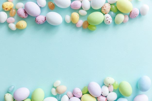 Wesołych świąt wielkanocnych. przygotowanie do wakacji. wielkanocne cukierki czekoladowe jajka i słodycze żelkowe na modnym pastelowym niebieskim kolorze. widok z góry prosty minimalizm płasko widok z góry.