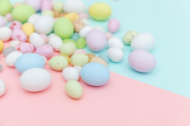 Wesołych świąt wielkanocnych. przygotowanie do wakacji. wielkanocne cukierki czekoladowe jajka i słodycze żelkowe na modnym pastelowym niebieskim różu. widok z góry prosty minimalizm płasko widok z góry.