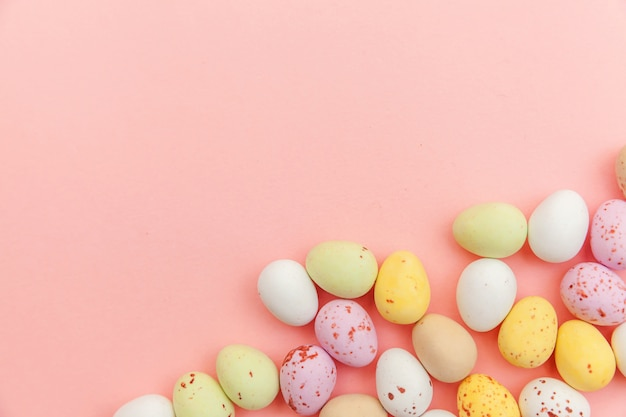 Wesołych świąt wielkanocnych. przygotowanie do wakacji. wielkanocne cukierki czekoladowe jajka i słodycze żelkowe na modnym pastelowym różu. widok z góry prosty minimalizm płasko widok z góry.