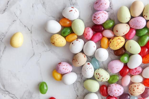 Wesołych świąt wielkanocnych. przygotowanie do wakacji. wielkanocne cukierki czekoladowe jajka i słodycze żelkowe na modnym szarym marmurze. widok z góry prosty minimalizm płasko widok z góry.