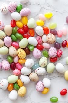 Wesołych świąt wielkanocnych. przygotowanie do wakacji. wielkanocne cukierki czekoladowe jajka i słodycze żelkowe na modnym szarym tle marmuru. widok z góry prosty minimalizm płasko widok z góry.