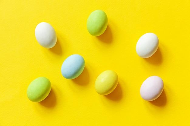 Wesołych świąt wielkanocnych. przygotowanie do wakacji. wielkanocne cukierki czekoladowe jajka kolorowe pastelowe słodycze i zabawka króliczka na modnym żółtym. widok z góry prosty minimalizm płasko widok z góry.