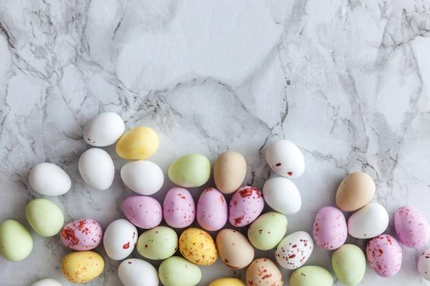 Wesołych świąt wielkanocnych. przygotowanie do wakacji. wielkanocne cukierki pastelowe czekoladowe jajka słodycze na modnym szarym marmurze. widok z góry prosty minimalizm płasko widok z góry.