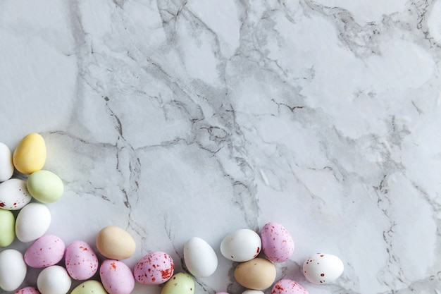 Wesołych świąt wielkanocnych. przygotowanie do wakacji. wielkanocne cukierki pastelowe czekoladowe jajka słodycze na modnym szarym tle marmuru. widok z góry prosty minimalizm płasko widok z góry.